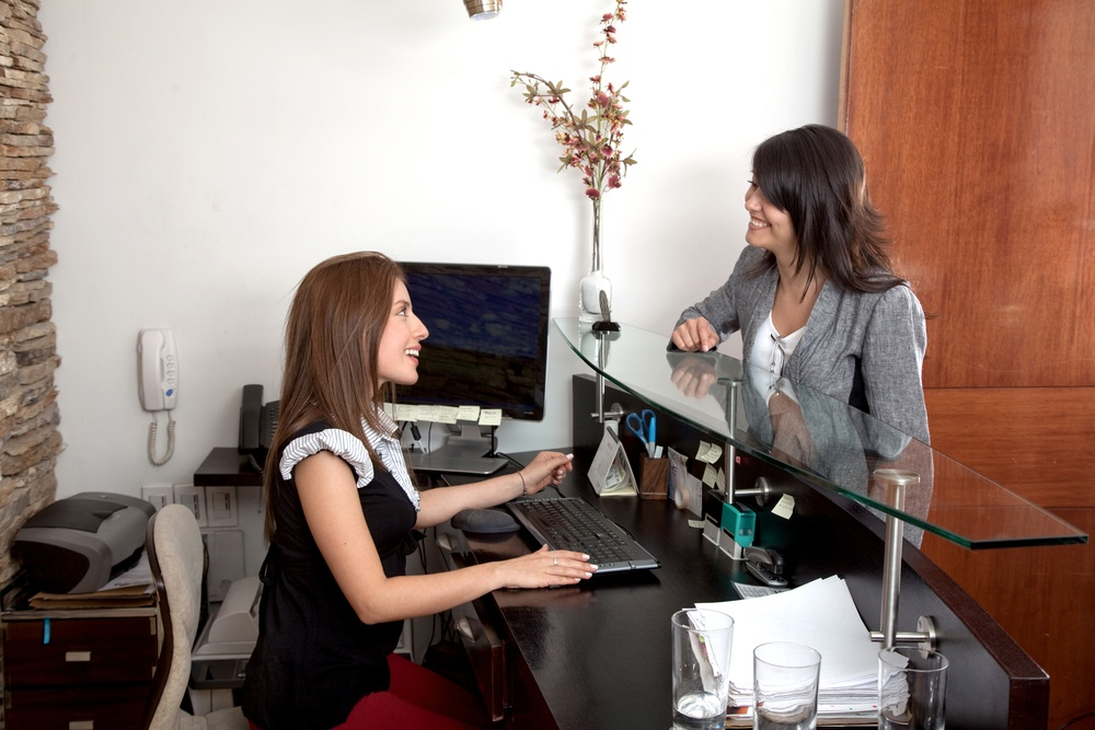Business woman being attended by the receptionist in an office