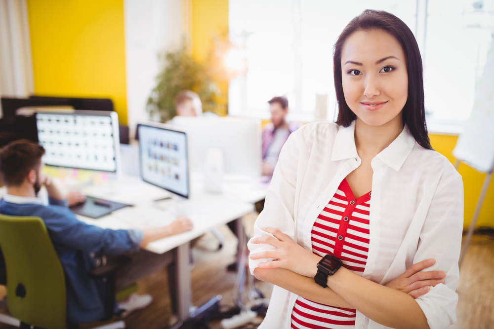 Portrait of beautiful young female executive standing at editing office