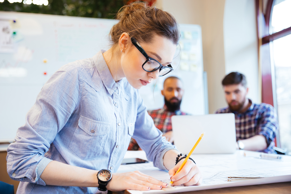 Woman engineer working on blueprint in office with colleagues on background-2
