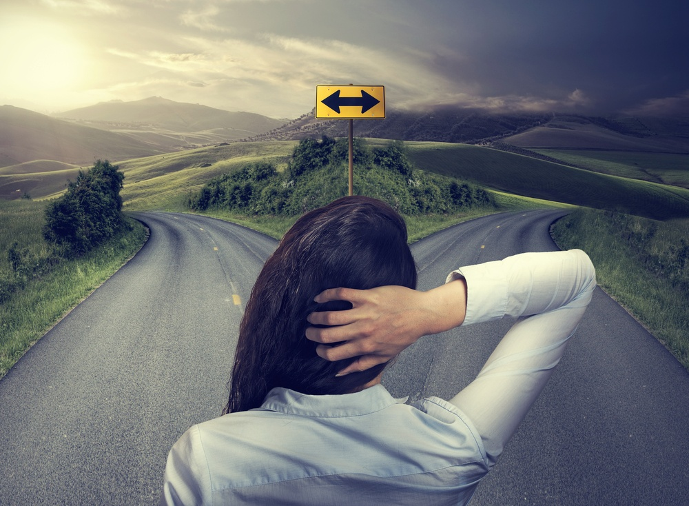 business woman in front of two roads thinking deciding hoping for best taking chance-1
