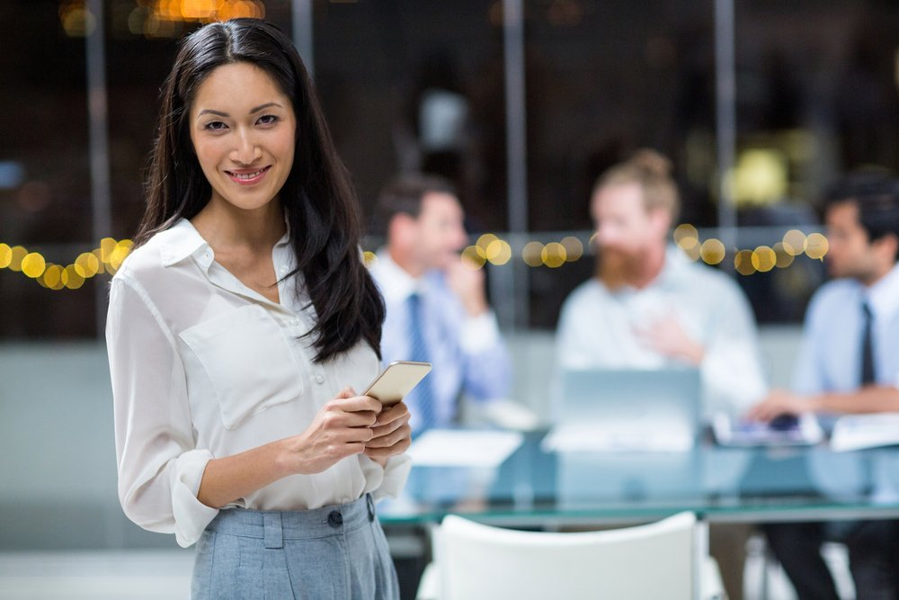 Businesswoman holding mobile phone in the office