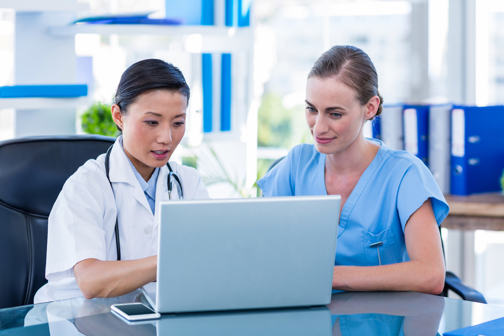 Doctor and nurse looking at laptop in medical office