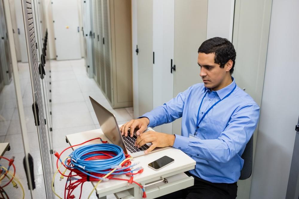 Focused technician working on laptop in server room.jpeg