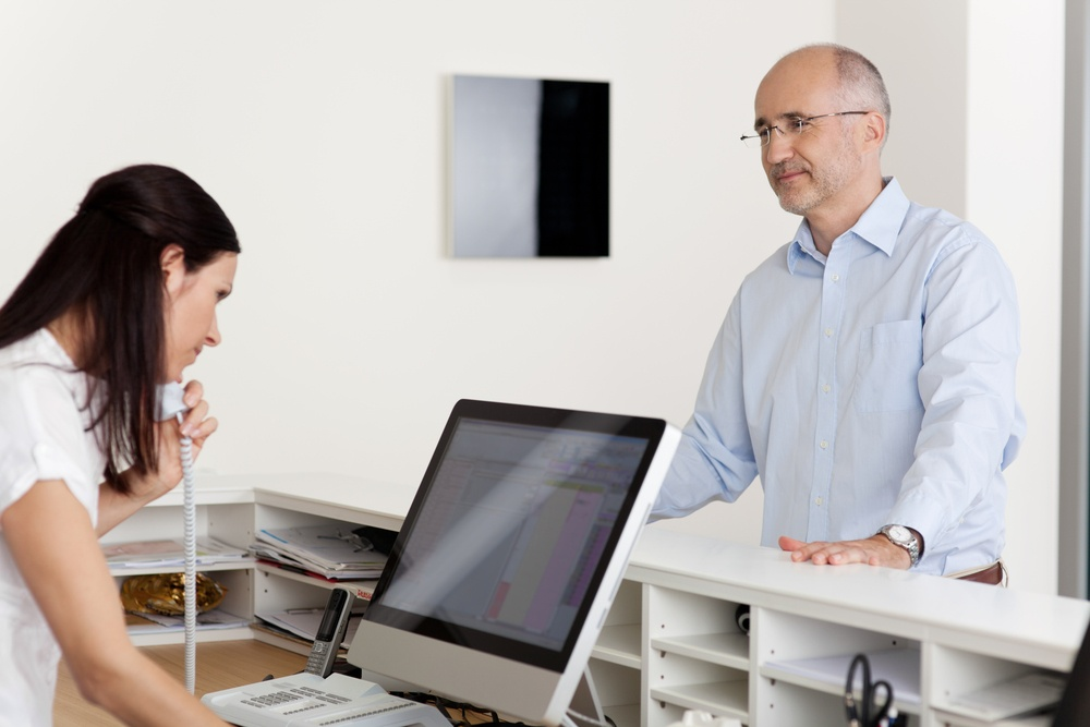 Mature male patient looking at female receptionist using landline phone and computer at reception in dentist's clinic.jpeg