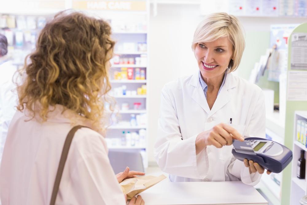 Pharmacist using card machine at pharmacy.jpeg