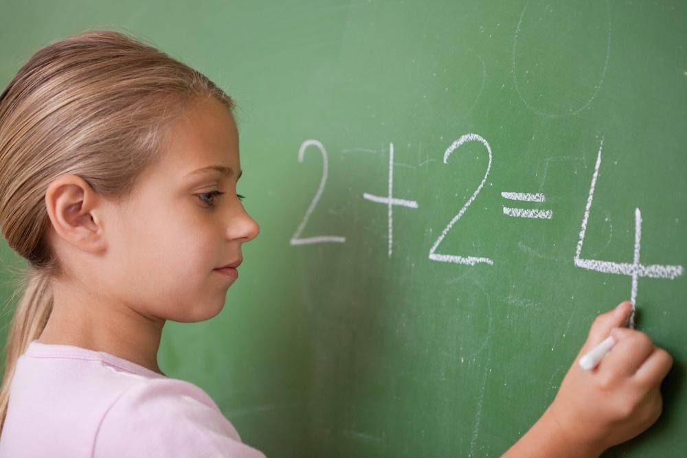 Schoolgirl writing a number on a blackboard.jpeg