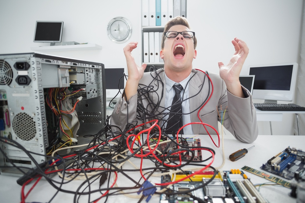 Stressed computer engineer working on broken cables in his office.jpeg