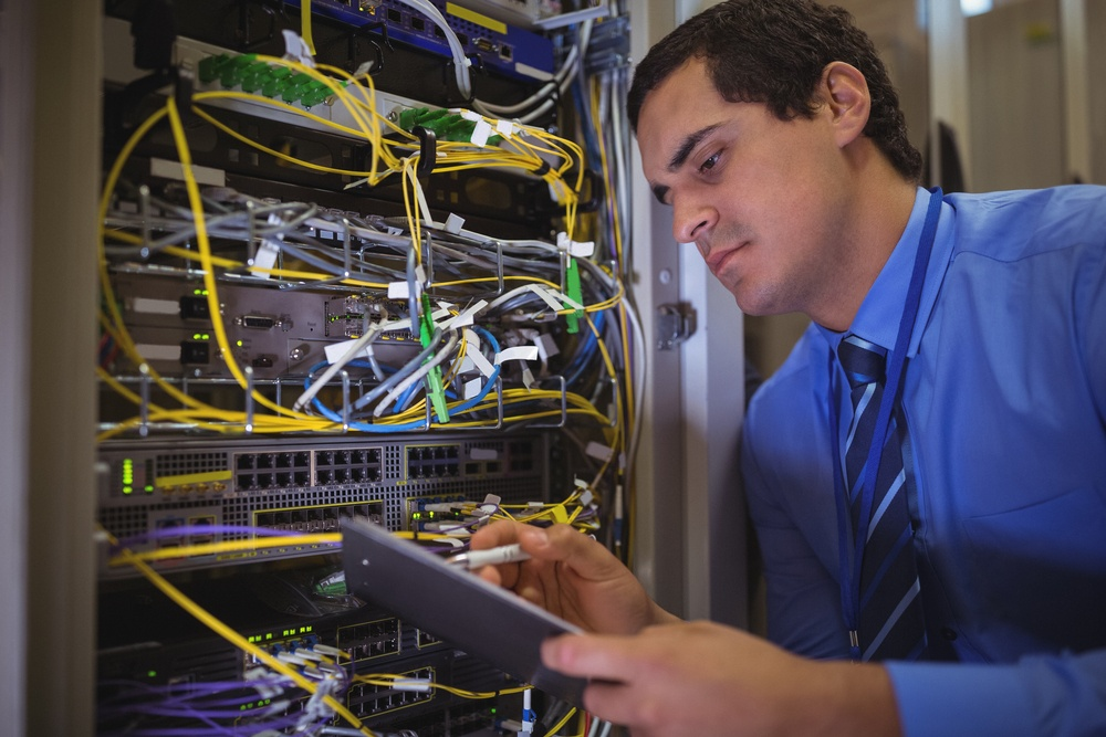 Technician maintaining record of rack mounted server on clipboard in server room.jpeg