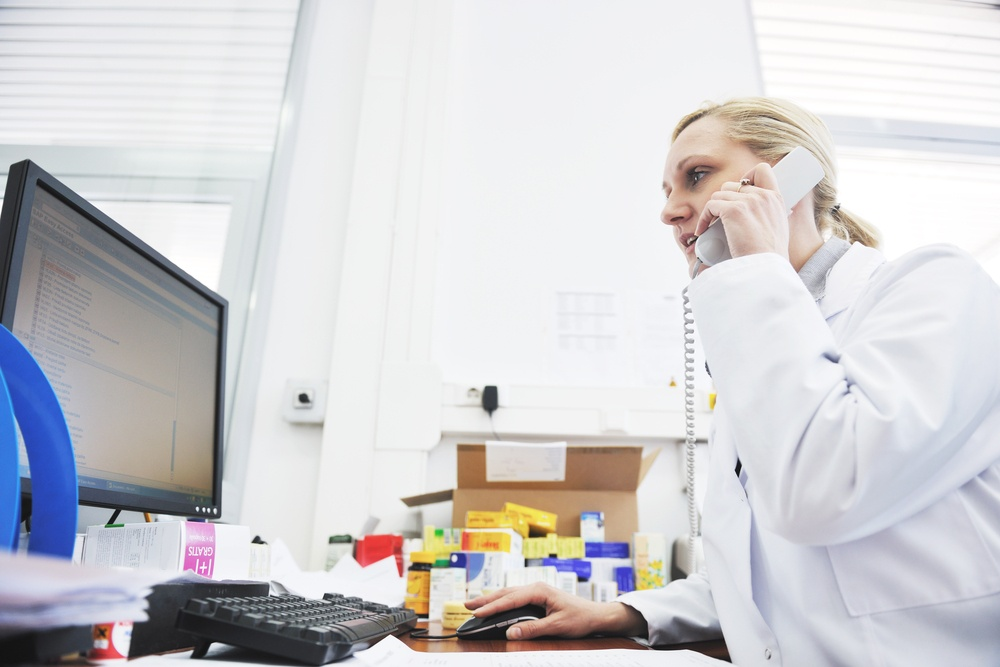 pharmacy worker talking by phone and typing and computer keyboard